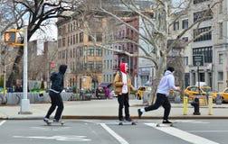 乘坐在城市街道纽约街市下东城的年轻行家孩子滑板 图库摄影