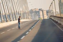 乘坐在城市道路桥梁的溜冰板者一只冰鞋 不劳而获s 免版税库存图片