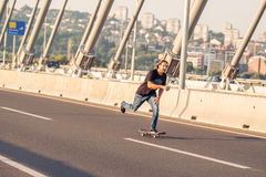 乘坐在城市道路桥梁的溜冰板者一只冰鞋 不劳而获s 免版税库存照片