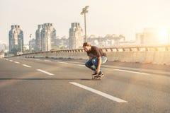 乘坐在城市道路桥梁的溜冰板者一只冰鞋 不劳而获s 库存图片