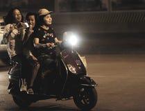 乘坐在小型摩托车的三个女孩 免版税图库摄影