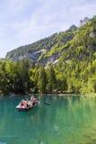 乘坐在小船的游人在Blausee或蓝色湖自然公园在夏天, Kandersteg,瑞士 免版税图库摄影
