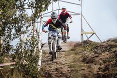 乘坐在山行迹的自行车的两位运动员 免版税库存图片