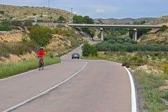 乘坐在惊人的风景的小山的骑自行车者 免版税库存照片