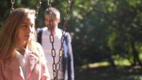 乘坐在摇摆和放松的美丽的年轻母亲 在背景中是她的家庭 在公园 4K 慢的行动 股票视频
