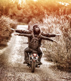 乘坐在摩托车高兴地 免版税库存图片