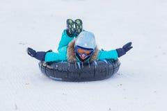 乘坐在有高山的一个雪撬的盔甲和玻璃的快乐的女孩 库存照片