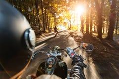 乘坐在机动车路的摩托车驾驶员 免版税库存照片