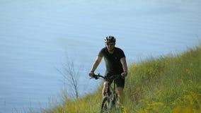 乘坐在河附近的骑自行车者 股票视频
