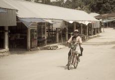 乘坐在沿一条空的街道的一辆自行车的贫穷男孩 免版税库存图片