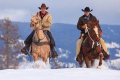 乘坐在深雪的两位牛仔 免版税图库摄影