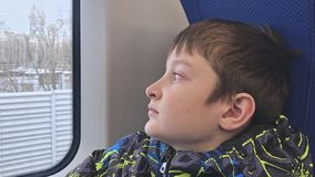 乘坐在火车的一个孤独的哀伤,沮丧和无动于衷的青春期前的男孩的画象,逃脱从家的他 股票视频