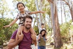 乘坐在父母在乡下的` s肩膀的孩子走 免版税库存照片
