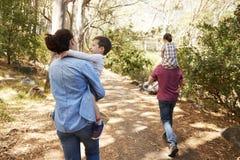 乘坐在父母在乡下的` s肩膀的孩子走 库存图片