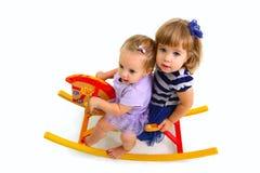 乘坐在玩具马的二个逗人喜爱的婴孩 免版税库存照片