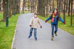 乘坐在秋天公园的两个孩子在直排轮式溜冰鞋 图库摄影