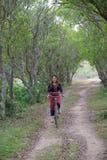 乘坐在米的一辆老自行车的年轻亚裔妇女调遣区域与 免版税库存照片