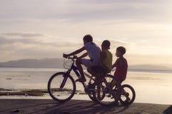 乘坐在自行车的三个男孩在海岸 剪影 免版税库存照片