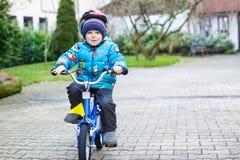 乘坐在自行车的三年的小孩秋天或winte 库存照片