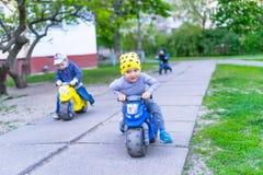 乘坐在自行车的滑稽的两个活跃小男孩在温暖的夏日 乡下 活跃休闲和体育孩子的 滑稽的逗人喜爱的chil 库存照片
