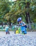乘坐在自行车的滑稽的两个活跃小男孩 免版税库存图片