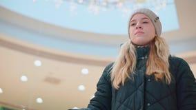 乘坐在购物中心的年轻可爱的女孩一个自动扶梯 下来 股票录像