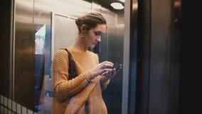 乘坐在透明电梯的观点的可爱的被注重的繁忙的白种人妇女使用智能手机移动式办公室app 股票视频