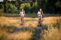 乘坐在道路的自行车的两个十几岁的女孩在领域 免版税库存照片