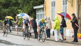 乘坐在雨中的三个骑自行车者 库存照片