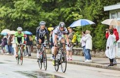 乘坐在雨中的三个骑自行车者 免版税库存图片