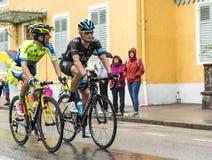 乘坐在雨中的两个骑自行车者 图库摄影