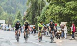 乘坐在雨中的四个骑自行车者 免版税库存图片