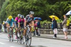 乘坐在雨中的小组骑自行车者 免版税库存照片