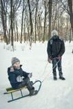 乘坐在雪橇的两个男孩在冬天 库存照片