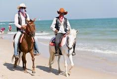 乘坐在马的人们在查家-上午海滩 免版税库存图片