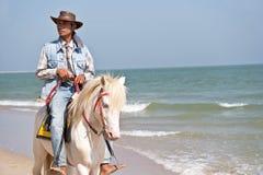 乘坐在马的人们在查家-上午海滩 库存图片