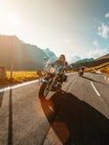 乘坐在高山高速公路的摩托车驾驶员日本大功率巡洋舰在著名Hochalpenstrasse,奥地利 免版税库存图片