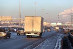 乘坐在高速公路路的卡车和汽车在冬天日落 免版税图库摄影