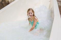 乘坐在水滑道下的逗人喜爱的小女孩在水公园 免版税库存照片