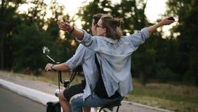 乘坐在electricbike的两个朋友在公园 乘坐与她的男朋友的太阳镜的年轻美丽的女孩 舒展 股票录像