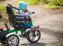 乘坐她的三轮车的热的逗人喜爱的女孩在春天公园 库存照片