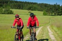 乘坐嬉戏夏天年轻人的自行车夫妇 图库摄影