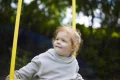乘坐摇摆的美丽的矮小的红头发人女孩在操场 免版税库存图片