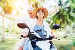 乘坐摩托车滑行车的愉快的快乐的微笑的夫妇旅客在棕榈树下 热带假期概念图象 免版税库存照片