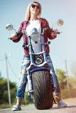 乘坐摩托车的女孩骑自行车的人在柏油路 免版税库存图片