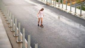 乘坐明亮的滑板的年轻美丽的白肤金发的女孩在桥梁 库存照片