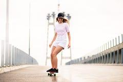 乘坐明亮的滑板的年轻美丽的白肤金发的女孩在桥梁 库存图片