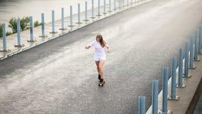 乘坐明亮的滑板的年轻美丽的白肤金发的女孩在桥梁 免版税库存照片