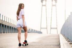 乘坐明亮的滑板的年轻美丽的白肤金发的女孩在桥梁 图库摄影
