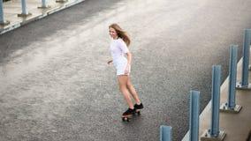 乘坐明亮的滑板的年轻美丽的白肤金发的女孩在桥梁 免版税库存图片